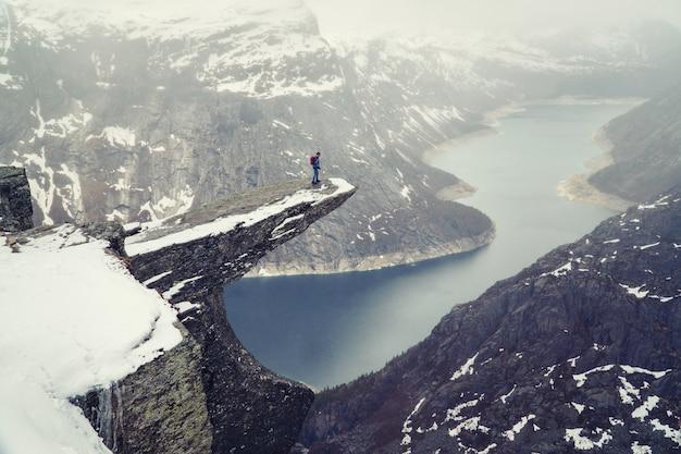Trolltunga-klippe unter schnee in norwegen. szenische landschaft. bemannen sie den reisenden, der auf rand des felsens steht und unten schaut. reisen, extremer und aktiver lebensstil.