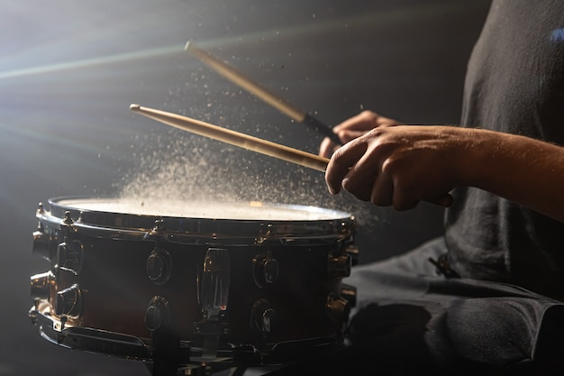 Trommelstöcke schlagen snare-drum mit spritzwasser auf schwarzem hintergrund unter bühnenbeleuchtung.
