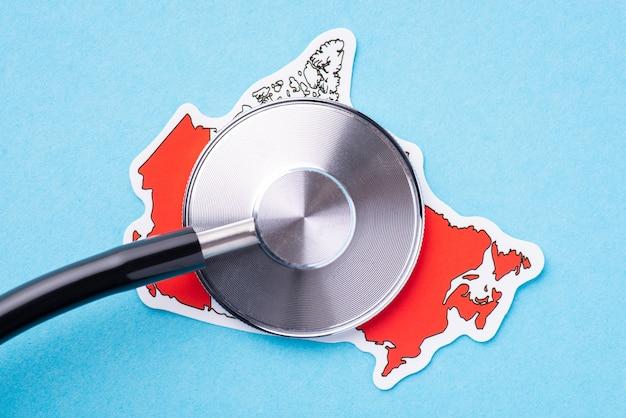Trommelteil des stethoskops auf einer karte von kanada