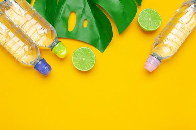 Tropenblätter und flaschenwasser auf gelbem hintergrund. entgiftungsfrucht hineingegossenes wasser.