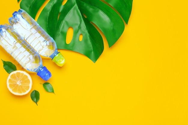 Tropenblätter und wasserflasche auf gelbem hintergrund. zitronenfrucht goss wasser hinein.