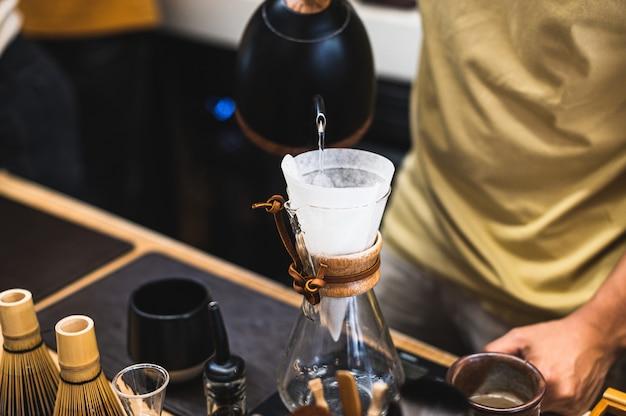 Tropfbrühen, gefilterter kaffee oder übergießen sind methoden, bei denen wasser über geröstete, gemahlene kaffeebohnen in einem filter gegossen wird