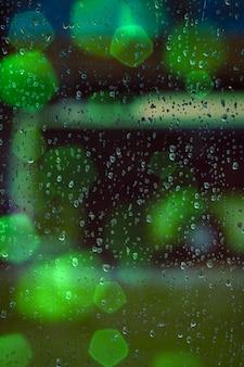 Tropfen am fenster und grüne bunte lichter in der nacht