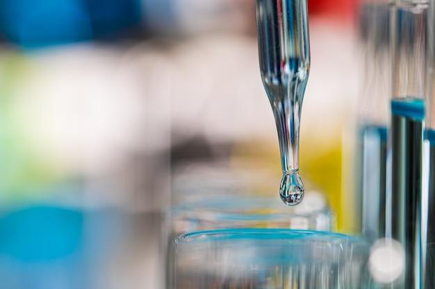 Tropfen blauer flüssigkeit vom tropfenfänger zum reagenzglas im labor mit hellem farbunschärfehintergrund. konzept des reinen und sauberen extrakts.