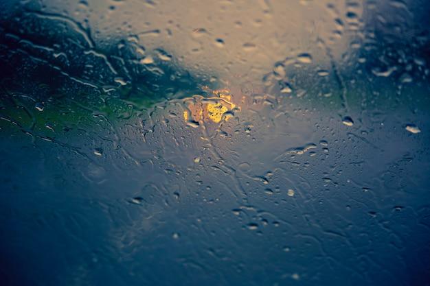 Tropfen des regens auf autowindschutzscheibe unten fließen. herbst-konzept. hintergrund