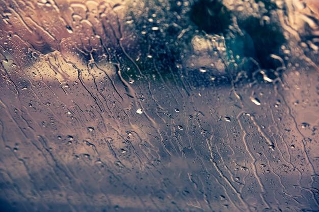Tropfen des regens auf autowindschutzscheibenhintergrund unten fließen