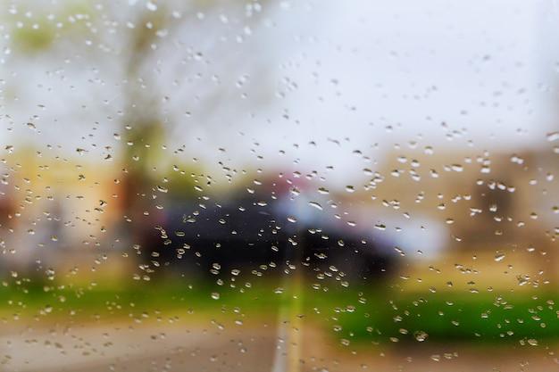 Tropfen des regens auf blauem glashintergrund. straße bokeh lichter unscharf.