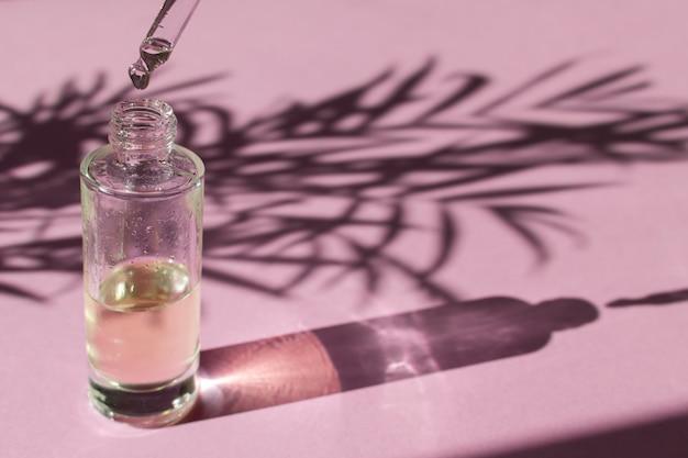 Tropfen fällt von einer pipette in eine glasflasche mit kosmetischem öl oder serum
