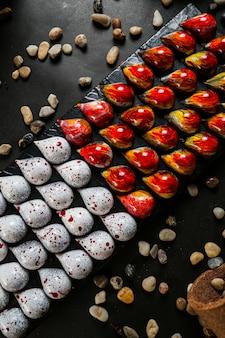 Tropfen form pralinen auf der schwarzen tafel rot gelb weiß seestein draufsicht