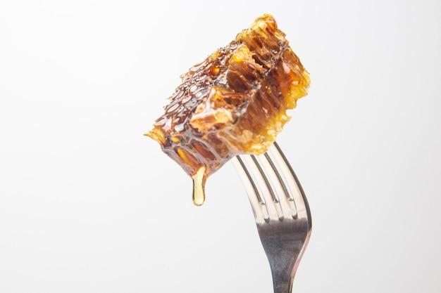 Tropfen frischen honigs tropfen von wachshonig auf eine tischgabel. vitaminernährung und bienenprodukt