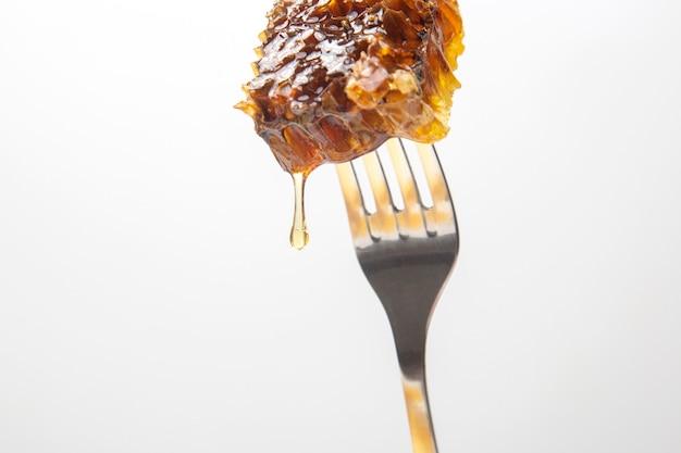 Tropfen frischer honig tropfen aus wachshonig auf eine tischgabel. vitaminernährung und bienenprodukt.