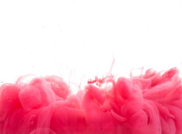 Tropfen roter farbe fallen auf dem wasser