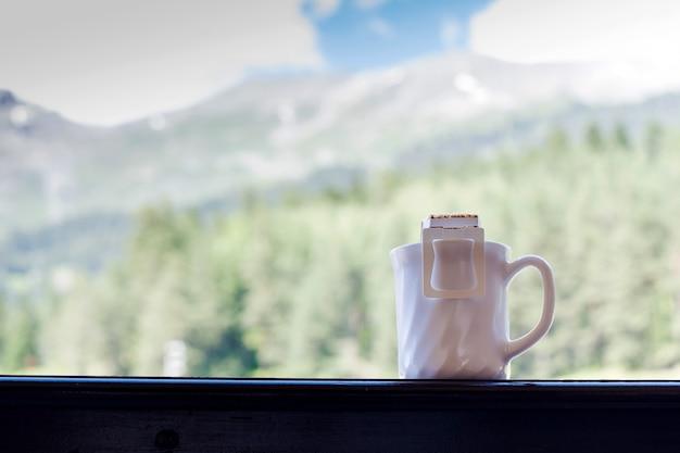 Tropfen sie kaffeebeutel in eine tasse vor dem hintergrund einer berglandschaft trends in der kaffeezubereitung