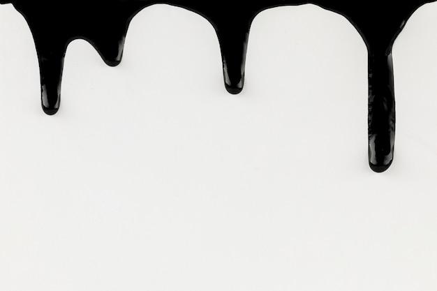 Tropfende schwarze farbe auf weißem hintergrund