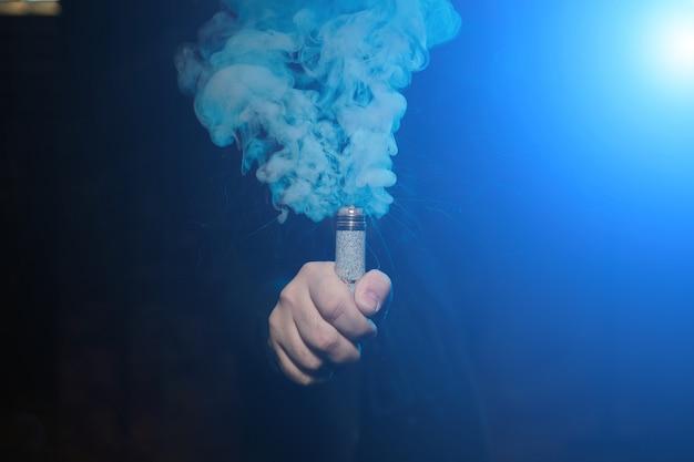 Tropfer in einer hand, der eine rauchwolke macht