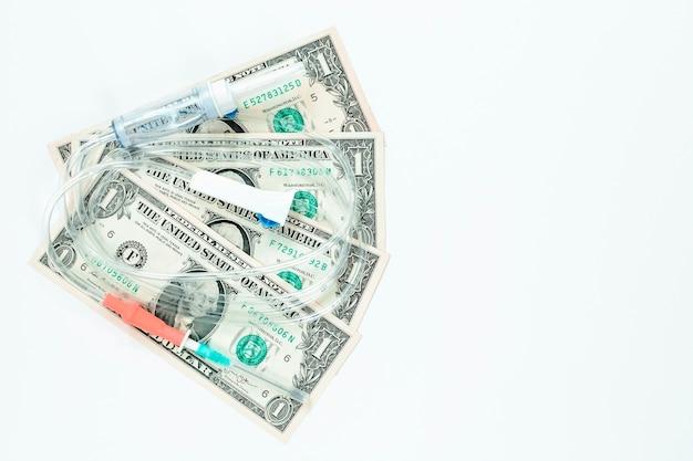 Tropfer mit dollar auf weißem hintergrund. konzept der behandlung und gesundheit.