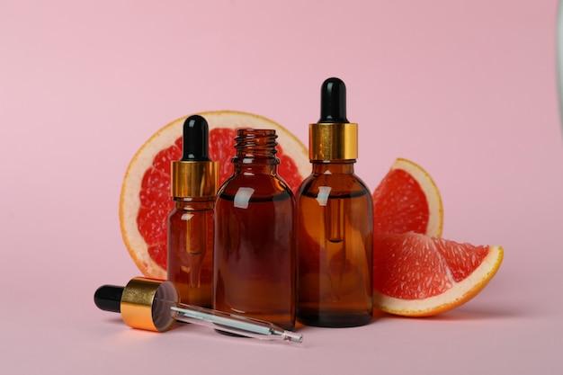 Tropfflaschen mit öl- und grapefruitscheiben auf rosa tisch