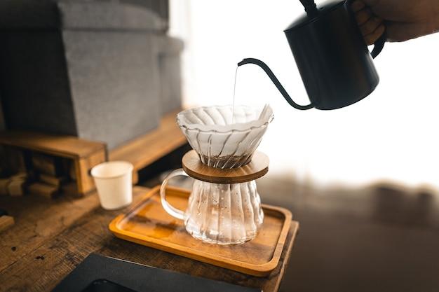 Tropfkaffee, barista gießt wasser auf kaffeesatz mit filter, kaffee brühen
