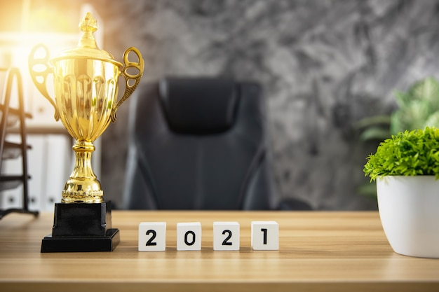 Trophäenpreis des gewinners mit niedlicher jahreszahl 2021 auf arbeitstisch im büro, erfolg und gewinnkonzept
