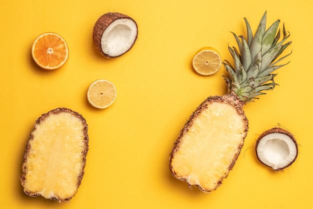 Tropische ananas, orangen, zitrone und kokosnuss auf einem pastellhintergrund.
