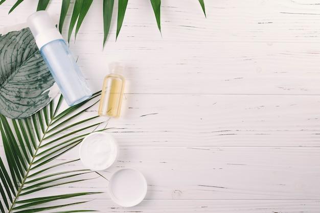 Tropische blätter der draufsicht mit schönheitswerkzeugen und -kosmetik