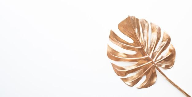 Tropische blätter in der goldfarbe auf weißem raumhintergrund. abstraktes monstera-blattdekorationsdesign