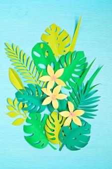 Tropische blätter und blumen des papiers über blauer pastellwand. exotischer sommerurlaub, draufsicht flach liegen