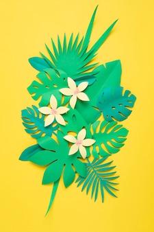 Tropische blätter und blumen des papiers über pastellwand. exotischer sommerurlaub, diy-projektidee. draufsicht flach liegen