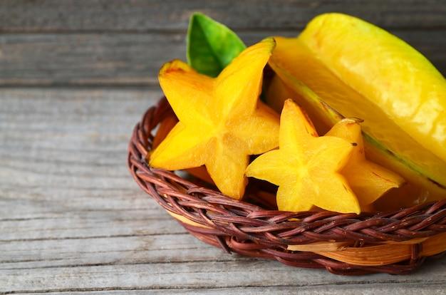 Tropische exotische frucht carambola in einem kleinen korb auf altem holztisch. starfruit oder averrhoa carambola hintergrund. gesundes essen, vegetarier oder diätkonzept.