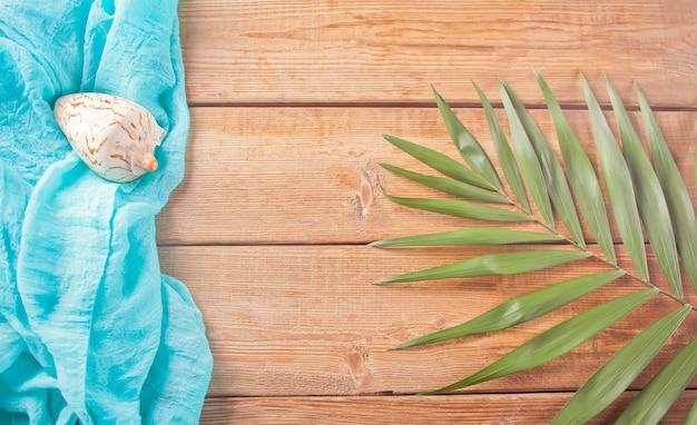 Tropische exotische palmblätter, blauer stoff und muschel auf hölzernem. ansicht von oben.