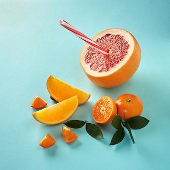 Tropische exotische zitrusfrüchte eine halbe grapefruit, mandarinen, orangenscheiben mit einem plastikstroh für saft auf blauem papierhintergrund
