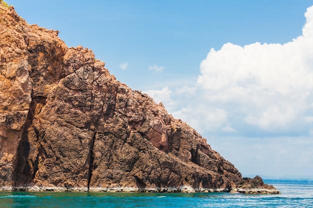 Tropische felseninsel und -meer auf blauem himmel