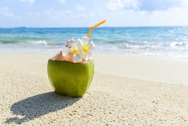 Tropische frucht der kokosnuss auf sandstrandhintergrundwasser - frischer kokosnusssaftsommer mit blume am strandmeer im heißen wetter ozeanlandschaftsnatururlaub im freien, junge kokosnuss