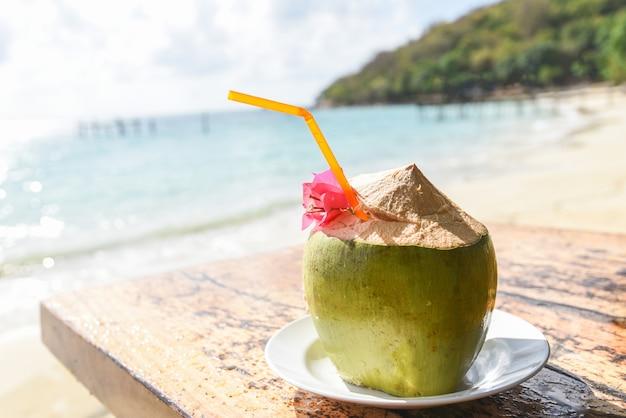 Tropische frucht der kokosnuss auf tisch und sandstrandwasser - frischer kokosnusssaftsommer mit blume am strandmeer im heißen wetter ozeanlandschaftsnatururlaub im freien, junge kokosnuss