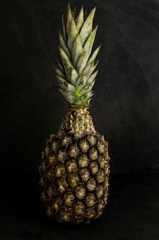 Tropische frucht: isolierte ananas, über schwarzem steinhintergrund.