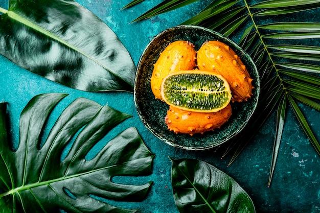 Tropische frucht kiwano-maracuja in der grünen schüssel auf türkis mit tropischen palmeblättern. ansicht von oben. tropisch
