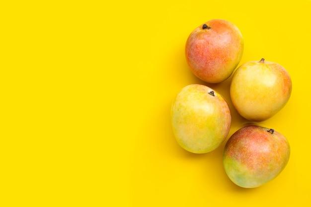 Tropische frucht, mango auf gelbem hintergrund. speicherplatz kopieren