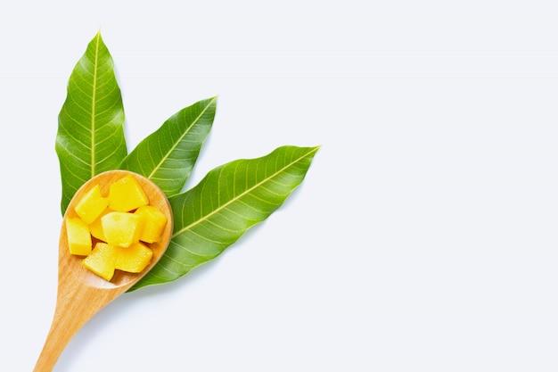 Tropische frucht, mangowürfelscheiben mit hölzernem löffel und blätter