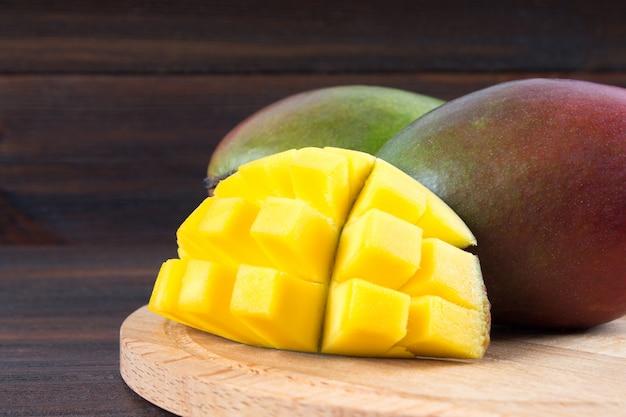 Tropische fruchtmango auf einem hölzernen hintergrund, ganz oder in scheiben geschnitten.
