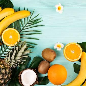 Tropische fruchtmischung und pflanzenblätter