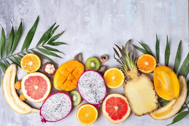 Tropische fruchtzusammenstellung auf einem hellen steinhintergrund mit palmblatt. draufsicht platz kopieren