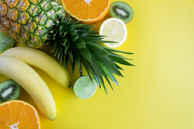 Tropische früchte auf dem gelben hintergrund. draufsicht.