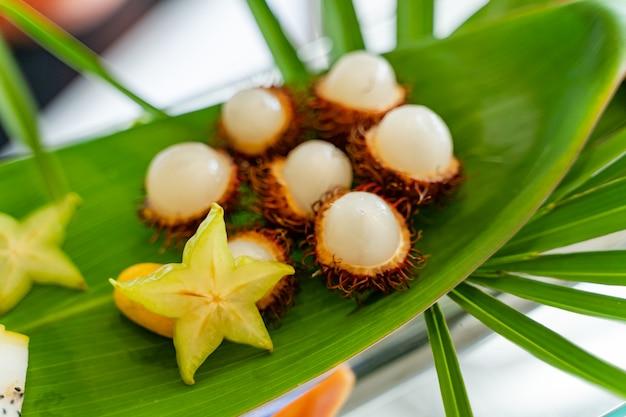 Tropische früchte auf einem großen grünen blatt draußen für gäste.