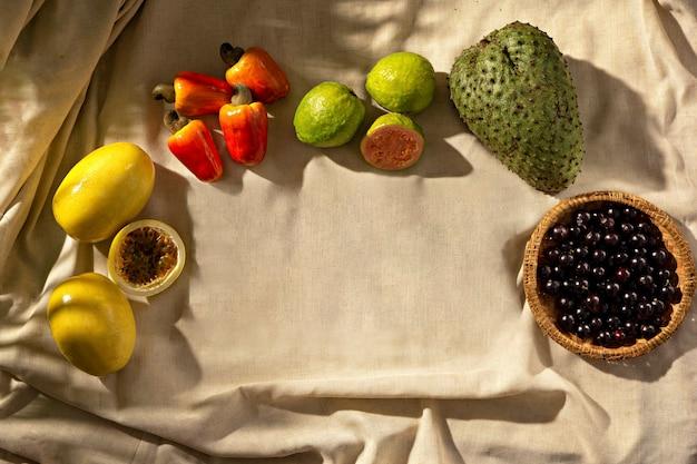 Tropische früchte auf stoffbasis, sonnenlicht, draufsicht. platz kopieren