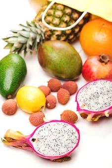 Tropische früchte auf weißem hintergrund. obstladen. exotische früchte aus papiereinkaufstasche.