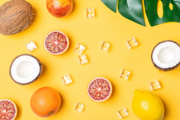 Tropische früchte, blutorangen, kokosnuss, palmblatt