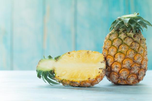 Tropische früchte des reifen ananassommers auf pastelltürkistabelle