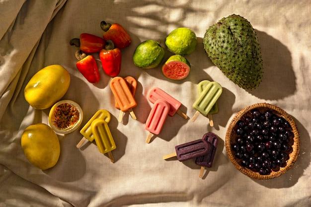 Tropische früchte eis am stiel mit tropischen früchten auf stoffunterlage, sonnenlicht, draufsicht
