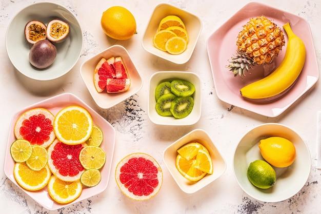 Tropische früchte ganz und scheiben auf tellern, draufsicht.