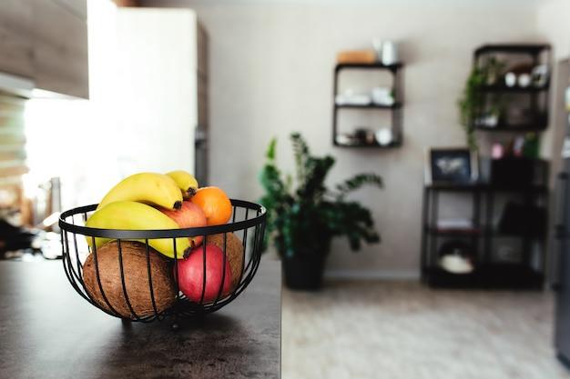 Tropische früchte: gebrochene kokosnuss, apfel, mandarine, orange, banane in obstschale auf bartheke in stilvoller dachbodenküche. unscharfer hintergrund. hochwertiges foto
